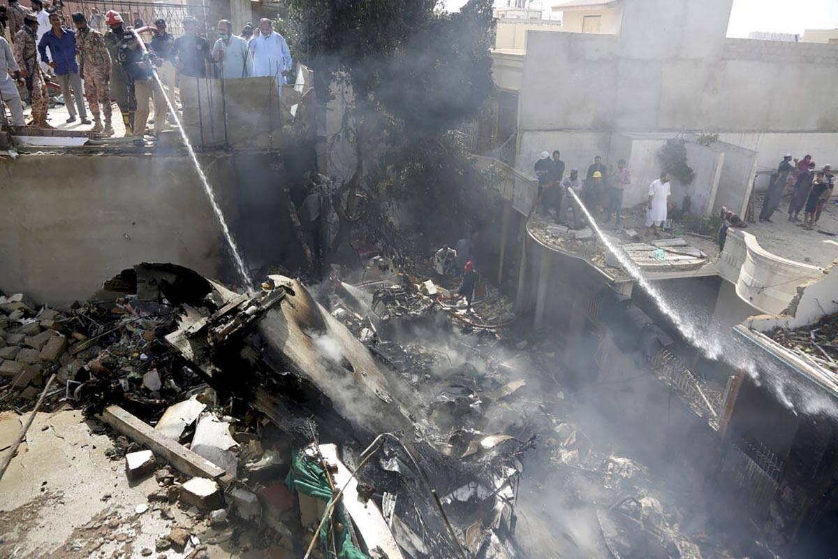 Fire brigade staff try to put out fire caused by plane crash in Karachi, Pakistan, Friday, May ...