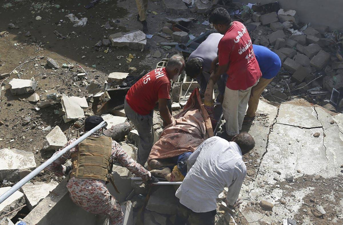 Volunteers carry the dead body of a plane crash victim at the site of a crash in Karachi, Pakis ...