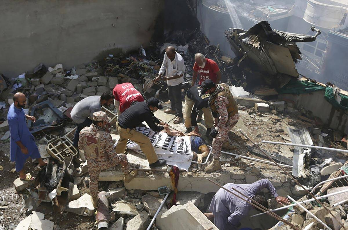 Volunteers cover the dead body of a plane crash victim at the site of the crash in Karachi, Pak ...