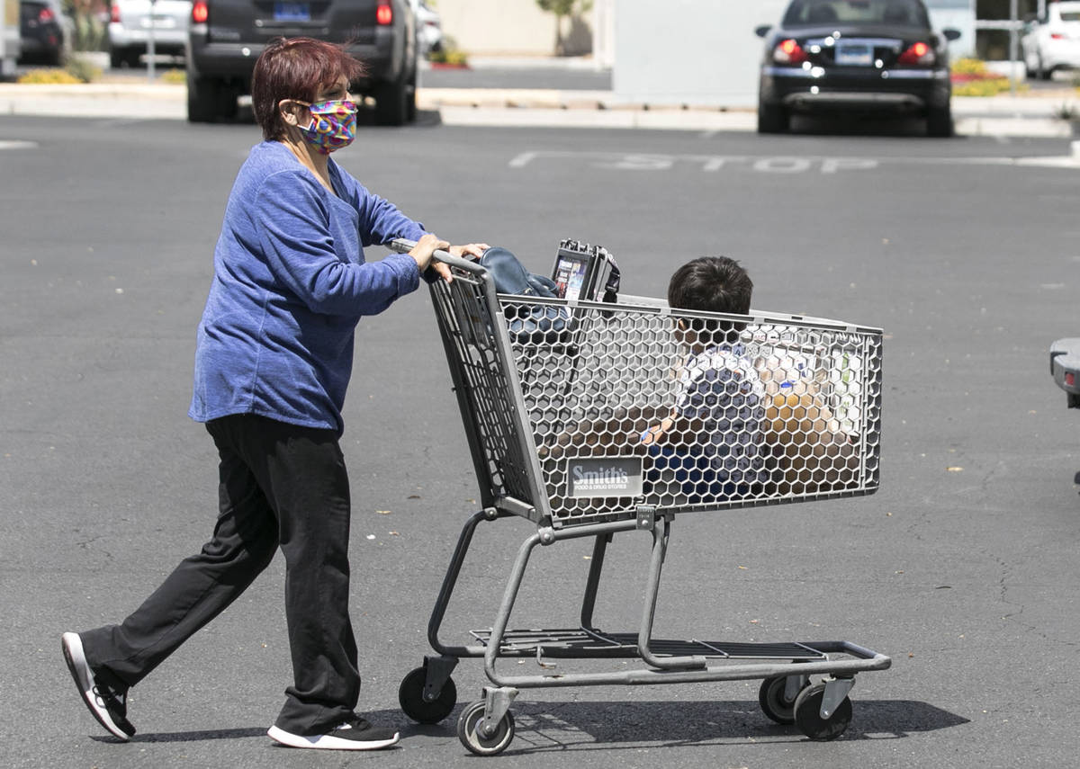 Lisha Valles, pushes her grandson, Phoenix Trejo, 3, in a grocery cart after shopping on Friday ...