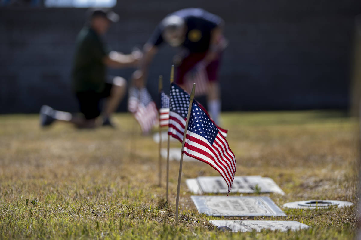 Frank Friedlander, left, and father Mort team up to plant more American flags on veteran's grav ...