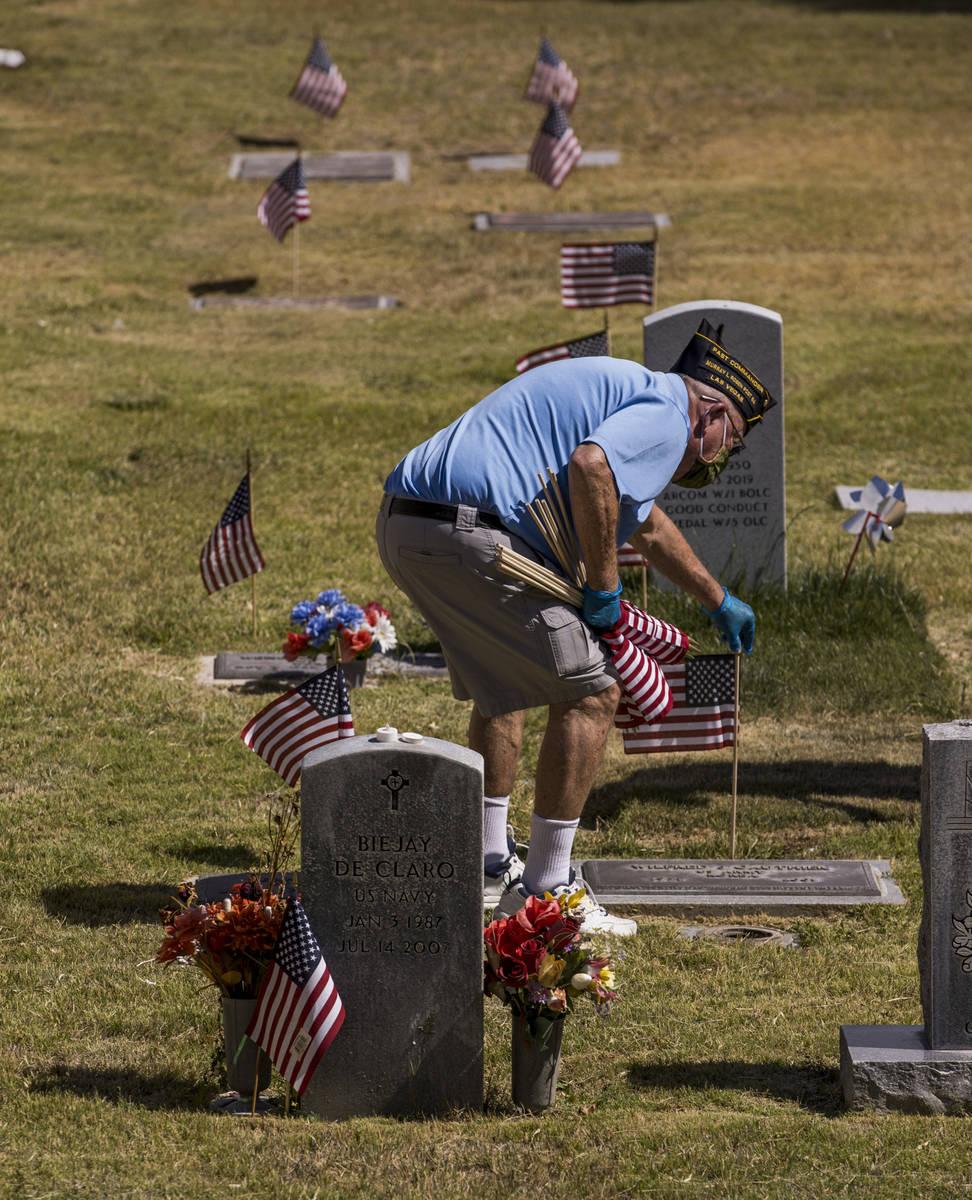 Retired Army Lt. Steve Seiden plants another American flag on veteran's graves in honor of Memo ...
