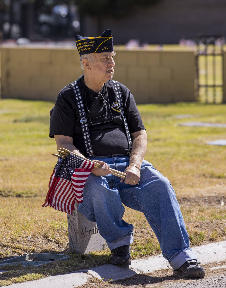 Army veteran Howard Greenspon takes a moment's rest while planting American flags on veteran's ...