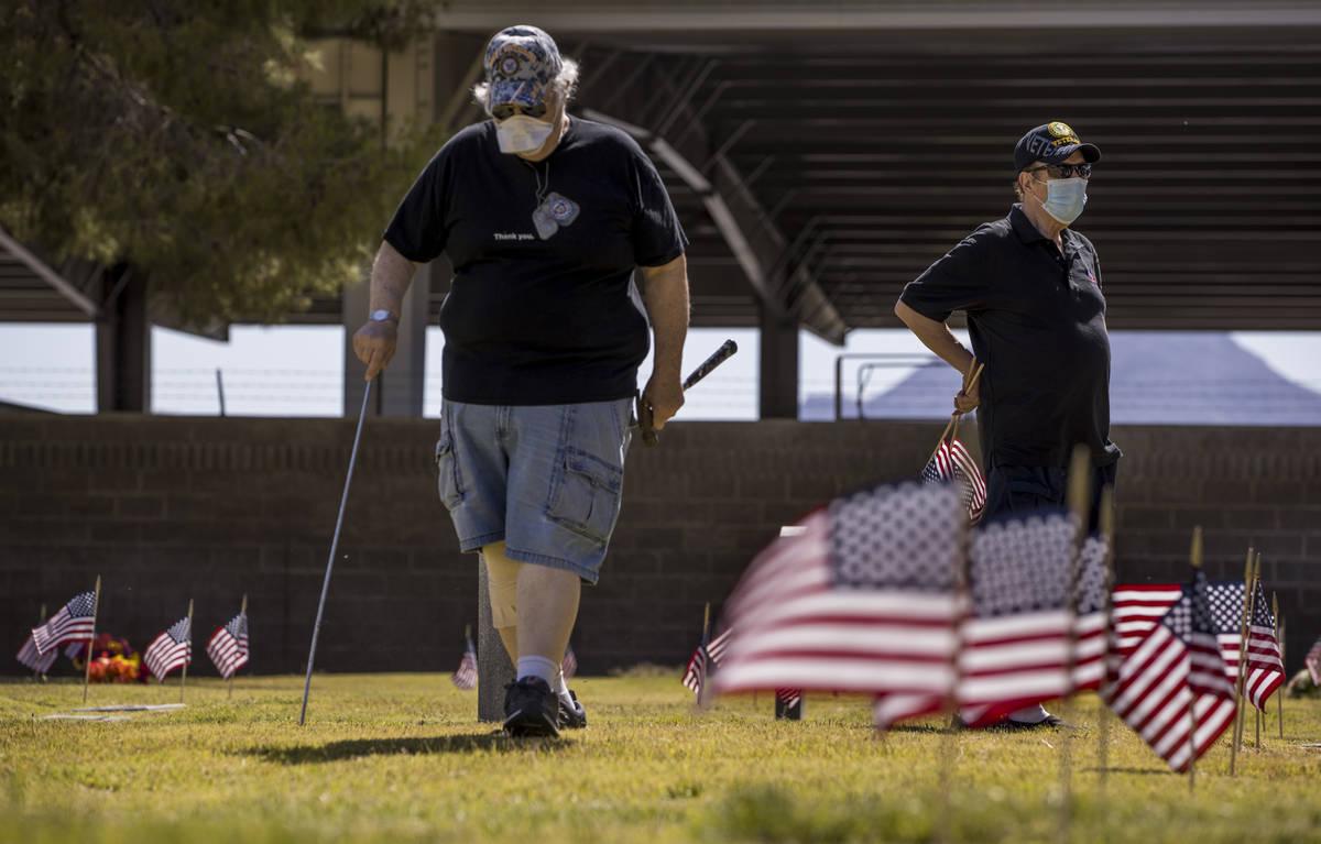 Marvin Botwinik, left, and Brendan Vargas help plant more American flags on veteran's graves in ...