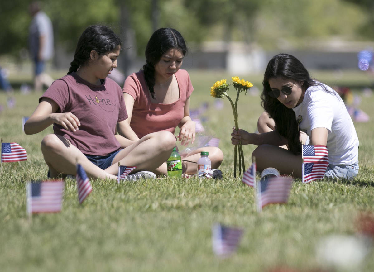 Jen Hernandez, right, and her sister, Alexandra, center, visit the grave site of their brother ...