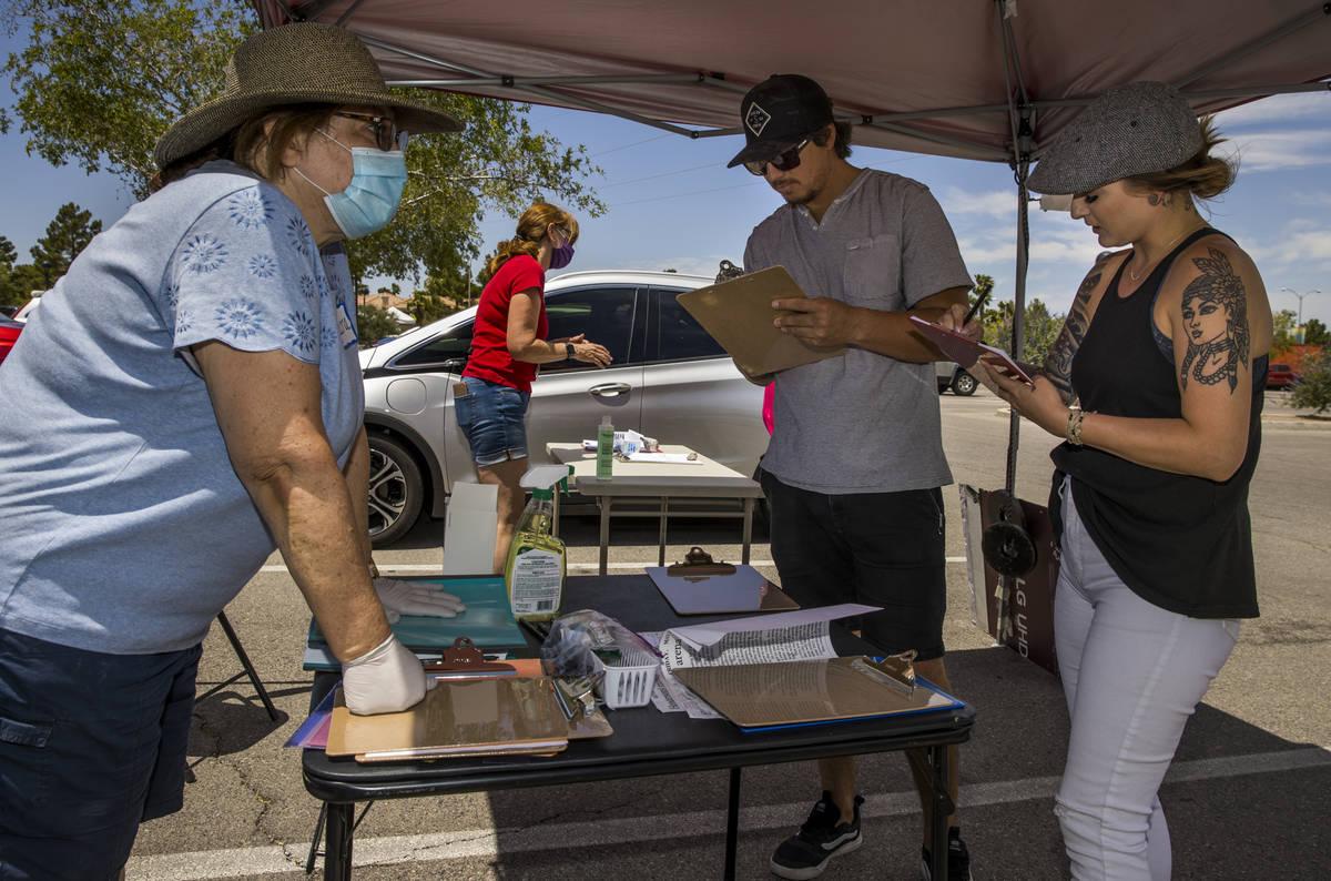 Henderson Coalition for Responsible Government volunteer Laura Sanchez, left, helps to get sign ...