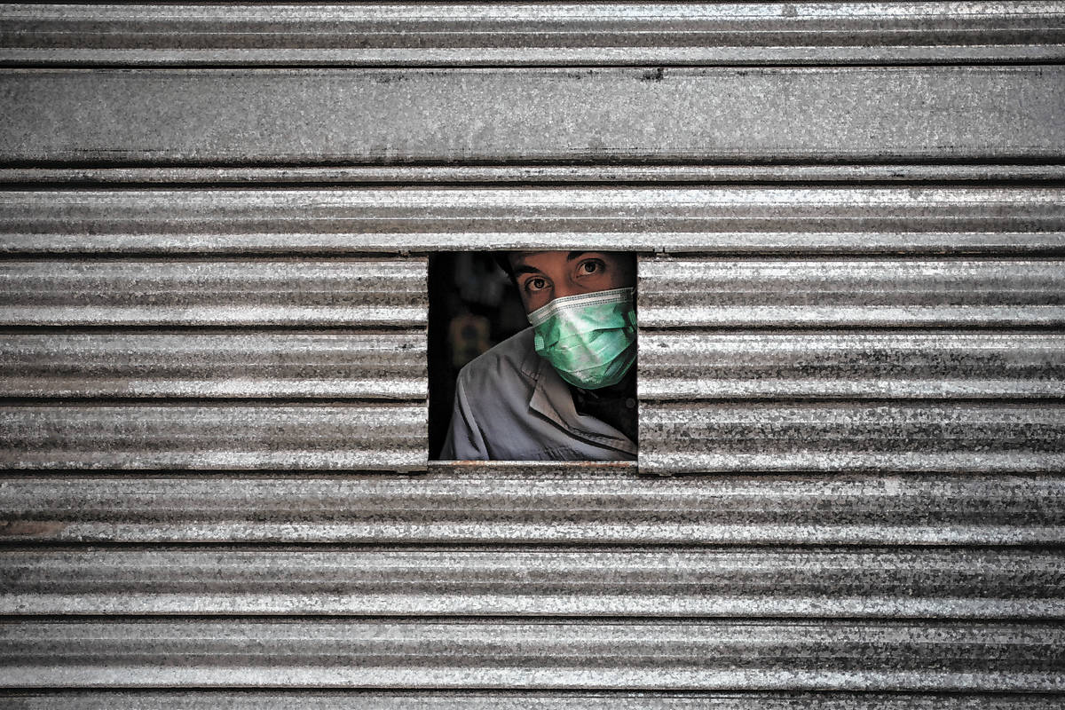 A man wearing a face mask looks out from a small opening on the door of a pharmacy as he waits ...