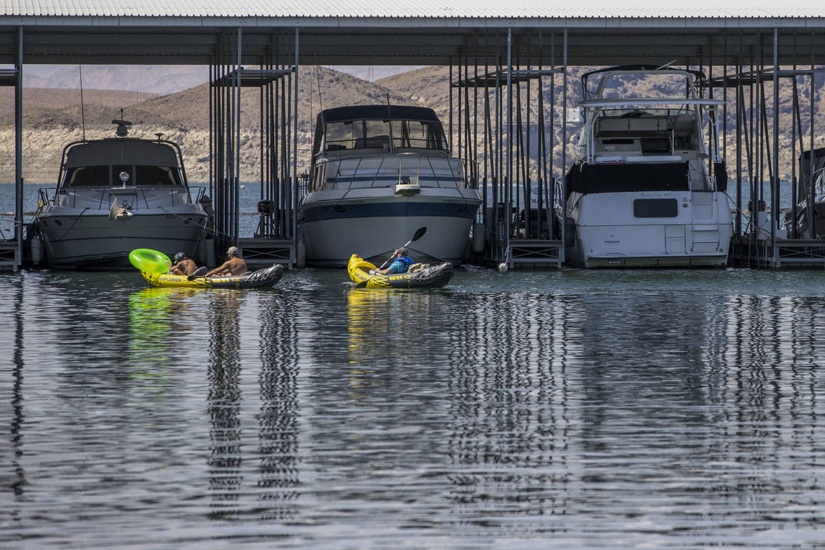 Kayakers move past moored boats at the Las Vegas Boat Harbor in the Lake Mead National Recreati ...