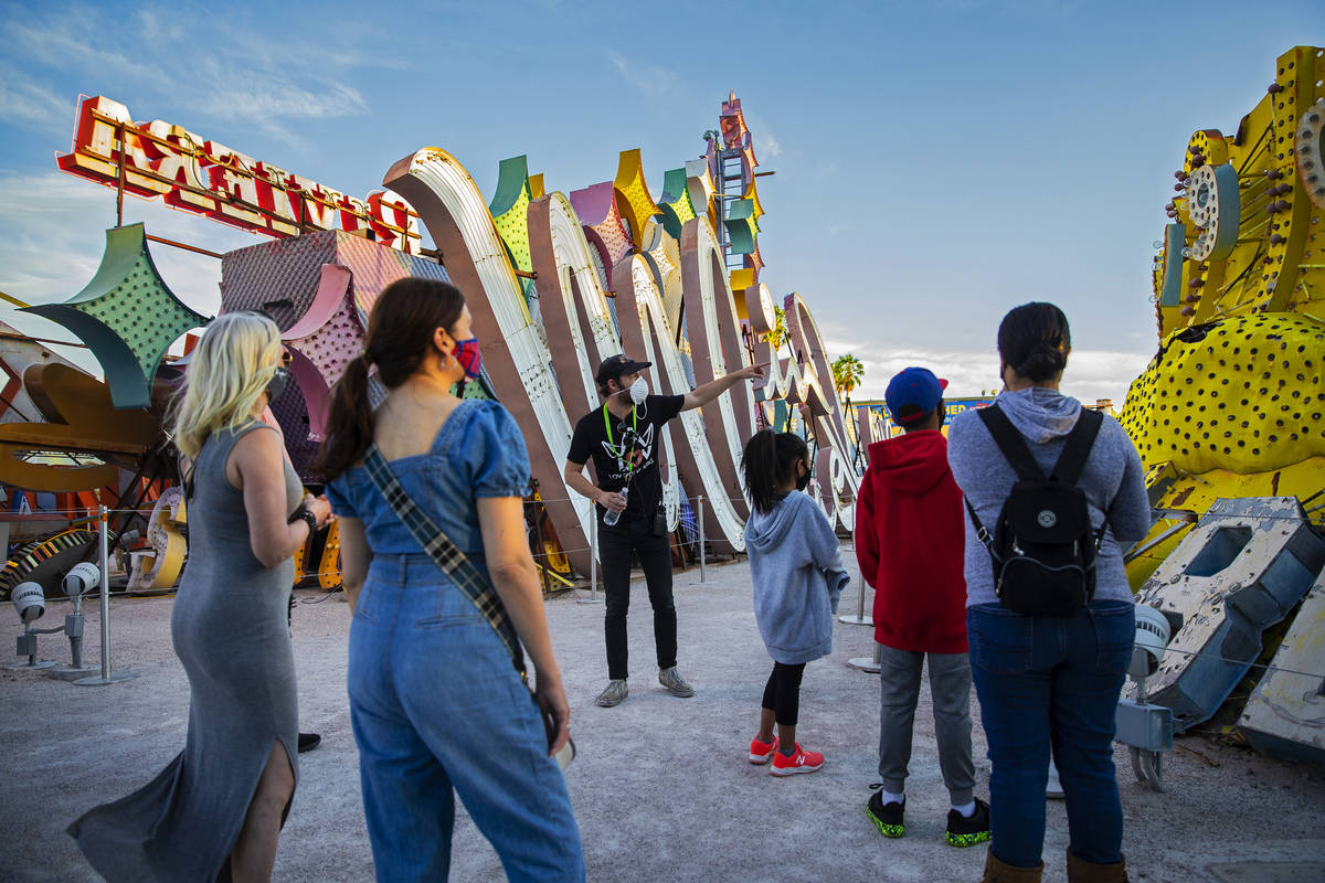 Interpreter Tyler Tingey, middle, leads a tour at The Neon Museum on Friday, May 22, 2020, in L ...