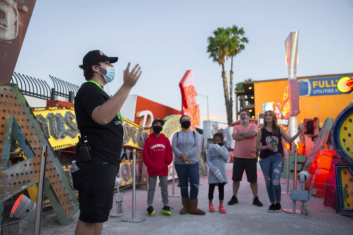 Interpreter Wyatt Currie, left, leads a tour at The Neon Museum on Friday, May 22, 2020, in Las ...