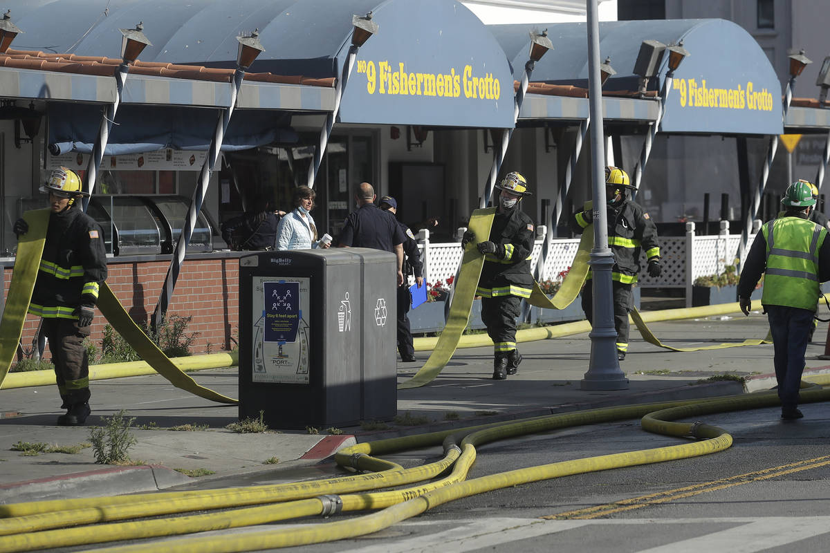 Fire officials carry a hose in front of The Grotto restaurant after a fire broke out before daw ...