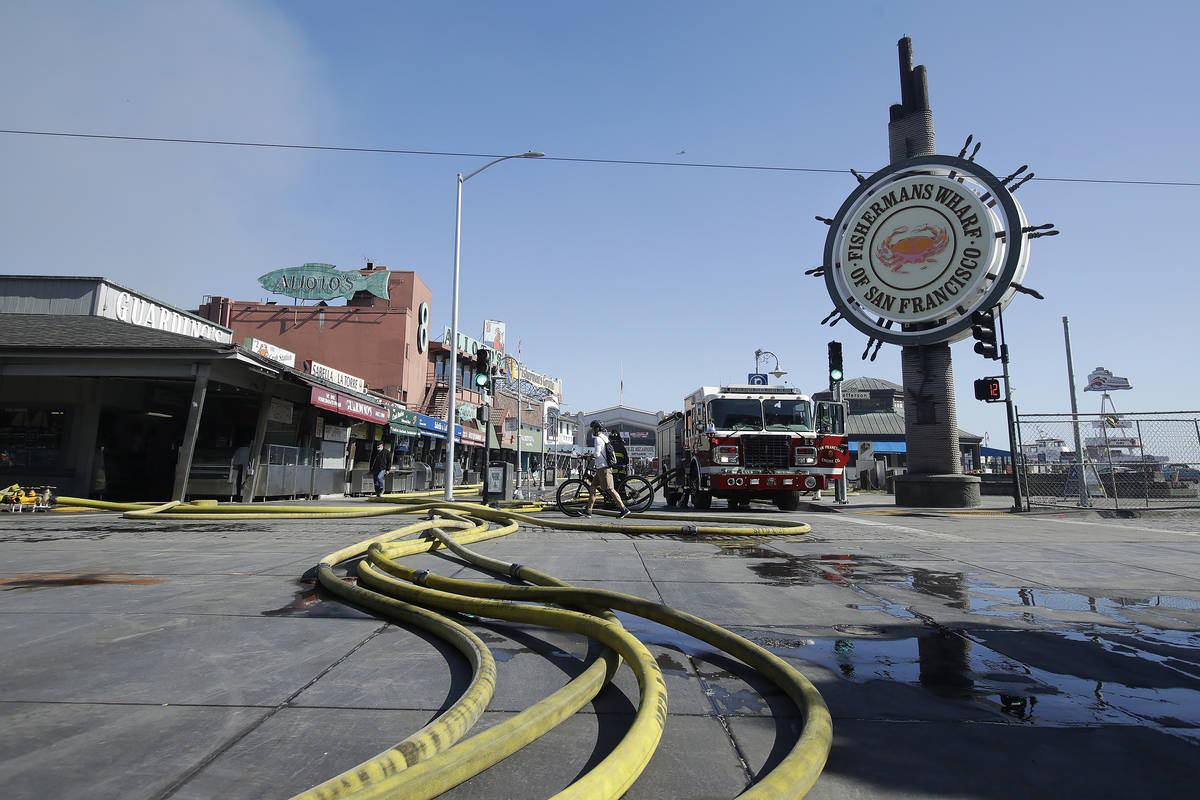 A runner passes over hoses after a fire broke out before dawn at Fisherman's Wharf in San Franc ...