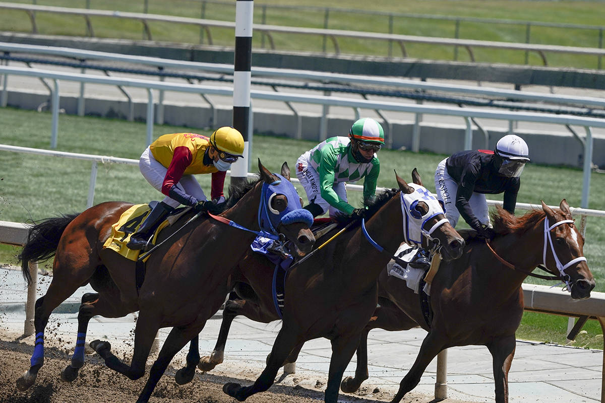 In this Friday, May 22, 2020 photo, jockeys wearing face masks ride in the first horse race at ...