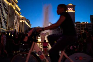 A biker passes the fountains at Caesars Palace on the Strip during Memorial Day weekend on Satu ...