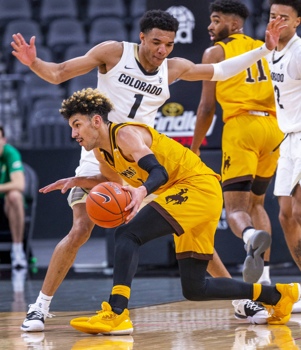 Colorado guard Tyler Bey (1, above) defends the lane over Wyoming guard Hunter Maldonado (24) d ...