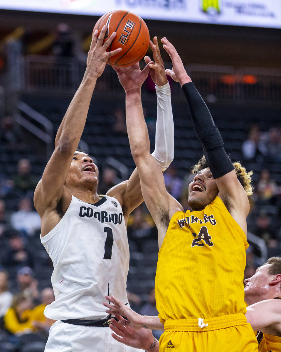 Colorado guard Tyler Bey (1, left) battles for a loose ball with Wyoming guard Hunter Maldonado ...