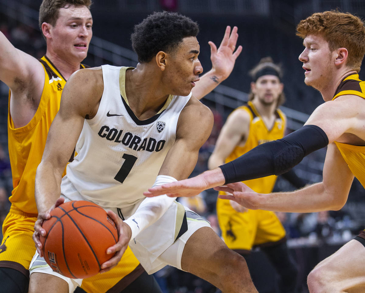 Colorado guard Tyler Bey (1, center) looks for a pass away from Wyoming guard Kenny Foster (22, ...