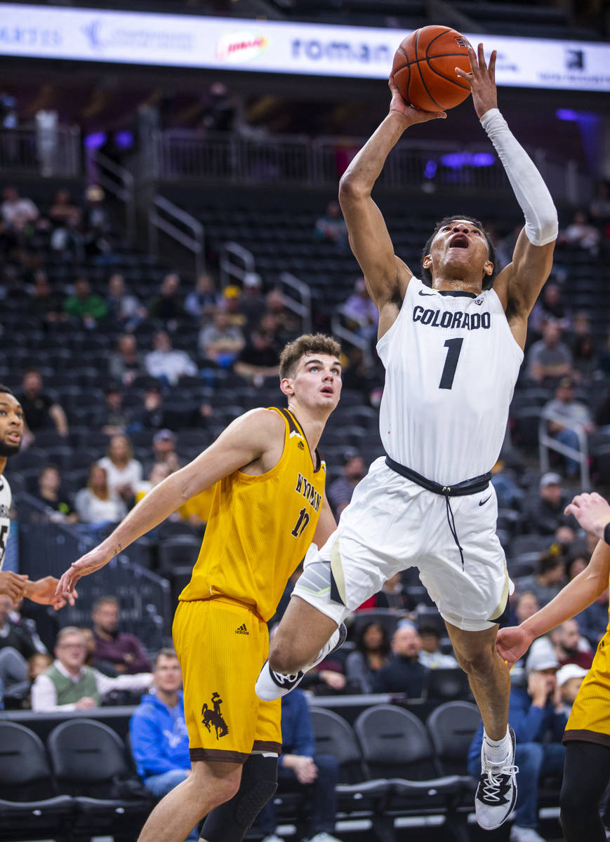 Colorado guard Tyler Bey (1) elevates for a shot with Wyoming forward Hunter Thompson (10) duri ...