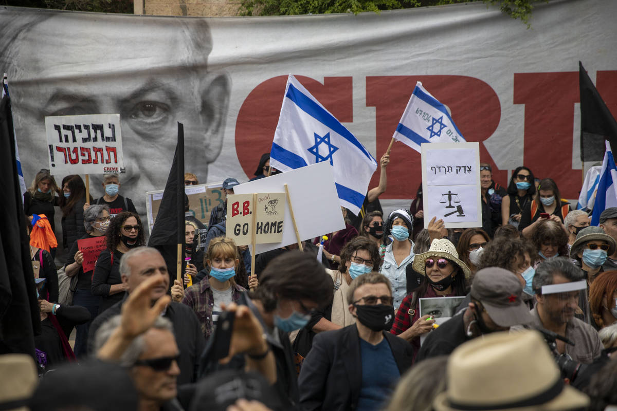 Protesters against Israel's Prime Minister Benjamin Netanyahu wave flags and banners outside hi ...