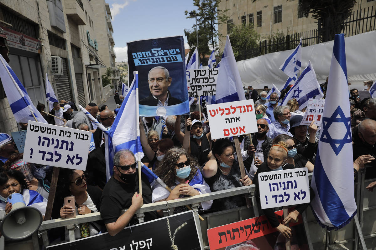 Israeli right wing activists hold flags and signs in support of Prime Minister Benjamin Netanya ...