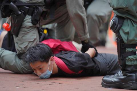A protester is detained by riot police during a demonstration against Beijing's national securi ...