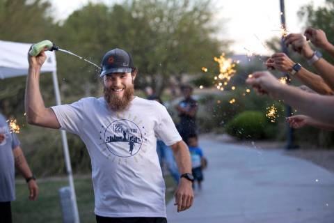 Peter Makredes cools off as his friends and family hold sparklers to encourage him as he runs f ...