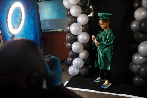 Dr. Dillard A. Scott takes a photo of Messiah Harris, 6, for his kindergarten graduation at Mr. ...