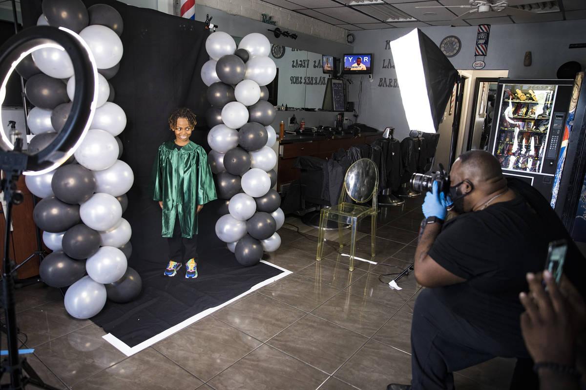 Dr. Dillard A. Scott takes a photo of Messiah Harris, 6, for his kindergarten graduation at Mr. ...