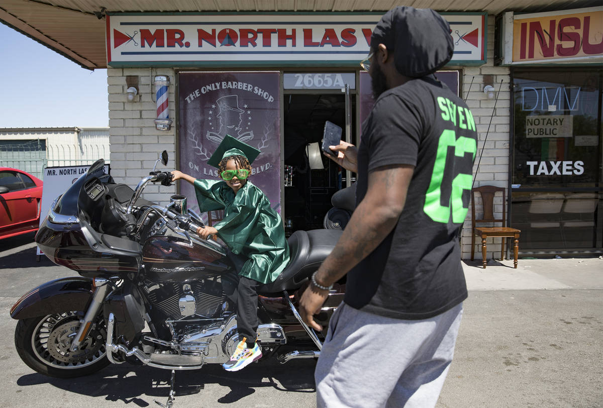 Morgan Harris takes a photo of his son Messiah Harris, 6, after having his kindergarten graduat ...