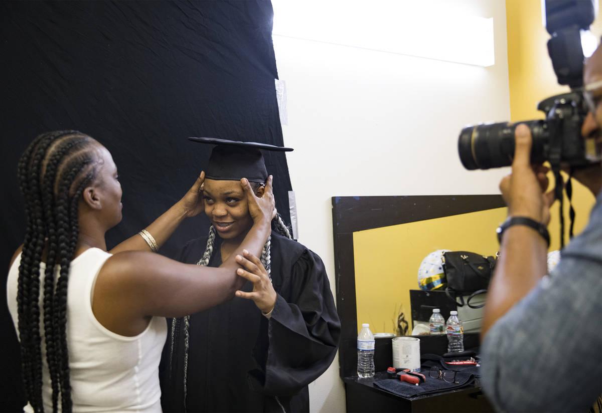 Kamika Adams adjusts the cap of her daughter Le 'Quitta Ragland, 18, as Julian Kemper takes a p ...
