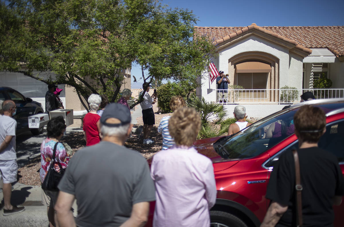 Friends and neighbors watch as Bob Altomondo, who played trumpet in the Navy, plays TAPS outsid ...