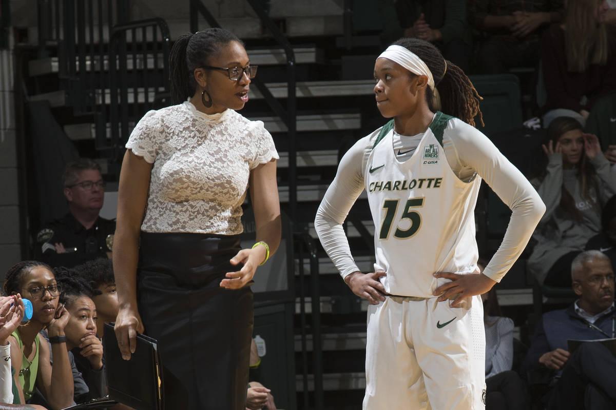 Charlotte women's basketball head coach Tanisha Wright talks with guard Jada McMillian. (Sam ...