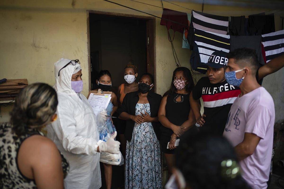 Relatives and friends of the late Eldon Cascais talk to a SOS Funeral worker wearing protection ...