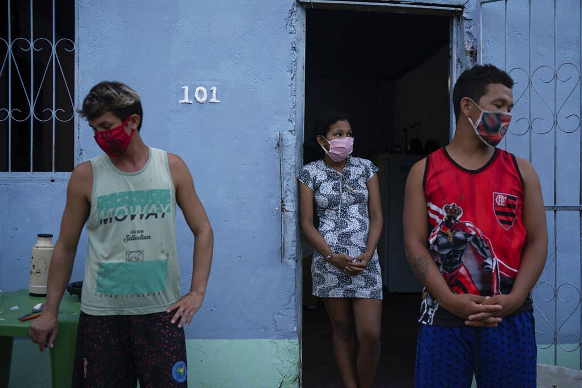 Caregiver Leandro Beiton, left, and relatives of the late Edgar Silva, wearing face masks amid ...