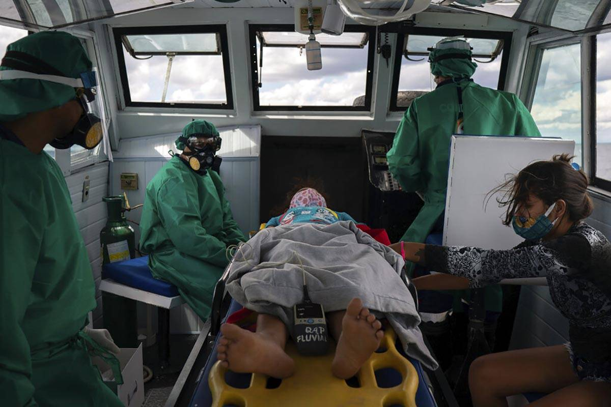 Fluvial emergency workers transfer by boat a 10-year-old suspected COVID-19 patient from a rive ...