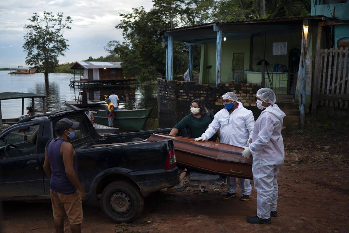 SOS Funeral workers move a coffin holding the body of an 86-year-old woman who lived by the Neg ...