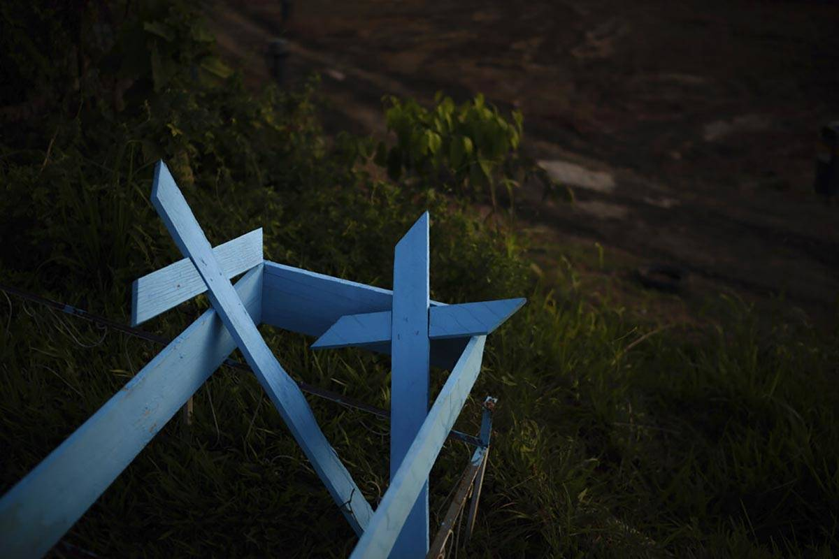 Painted wooden crosses lay on the roadside of a new section of the Nossa Senhora Aparecida ceme ...
