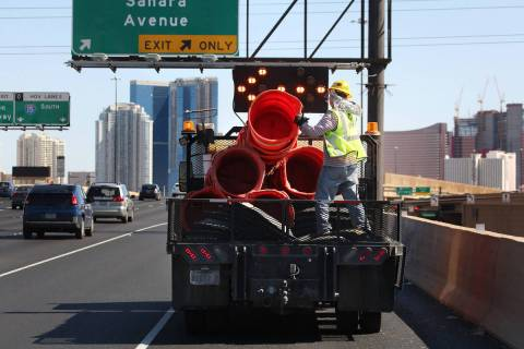 Crews work to remove orange safety barrels along Interstate 15 near the Sahara Avenue exit on M ...