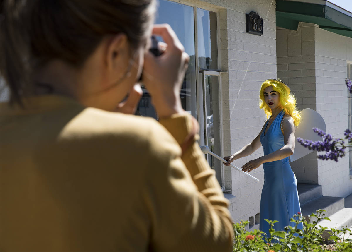 Holly Rae Vaughn takes a photo of Victoria Hogan, dressed as the Blue Angel statue from the fo ...