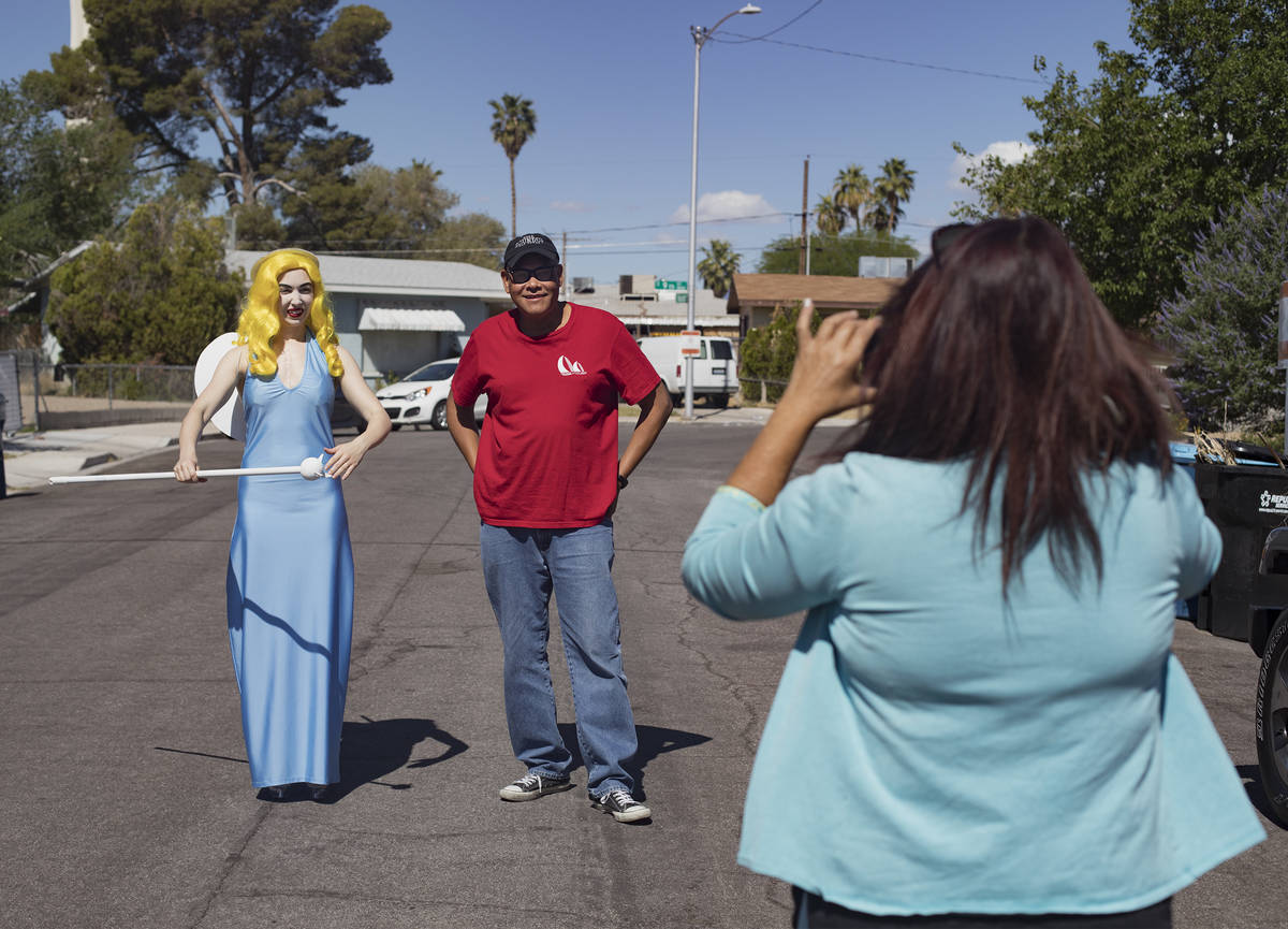 Victoria Hogan, dressed as the Blue Angel statue from the former Blue Angel Motel, takes a phot ...