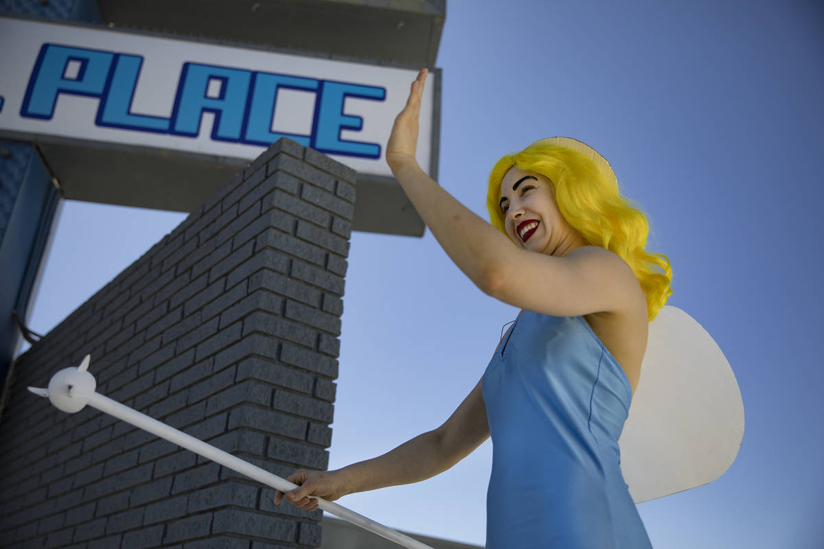 Victoria Hogan, dressed as the Blue Angel statue from the former Blue Angel Motel, waves at bys ...