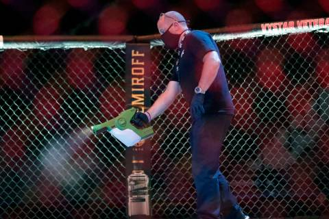 A worker sprays sanitizer in the octagon between bouts during a UFC 249 mixed martial arts comp ...