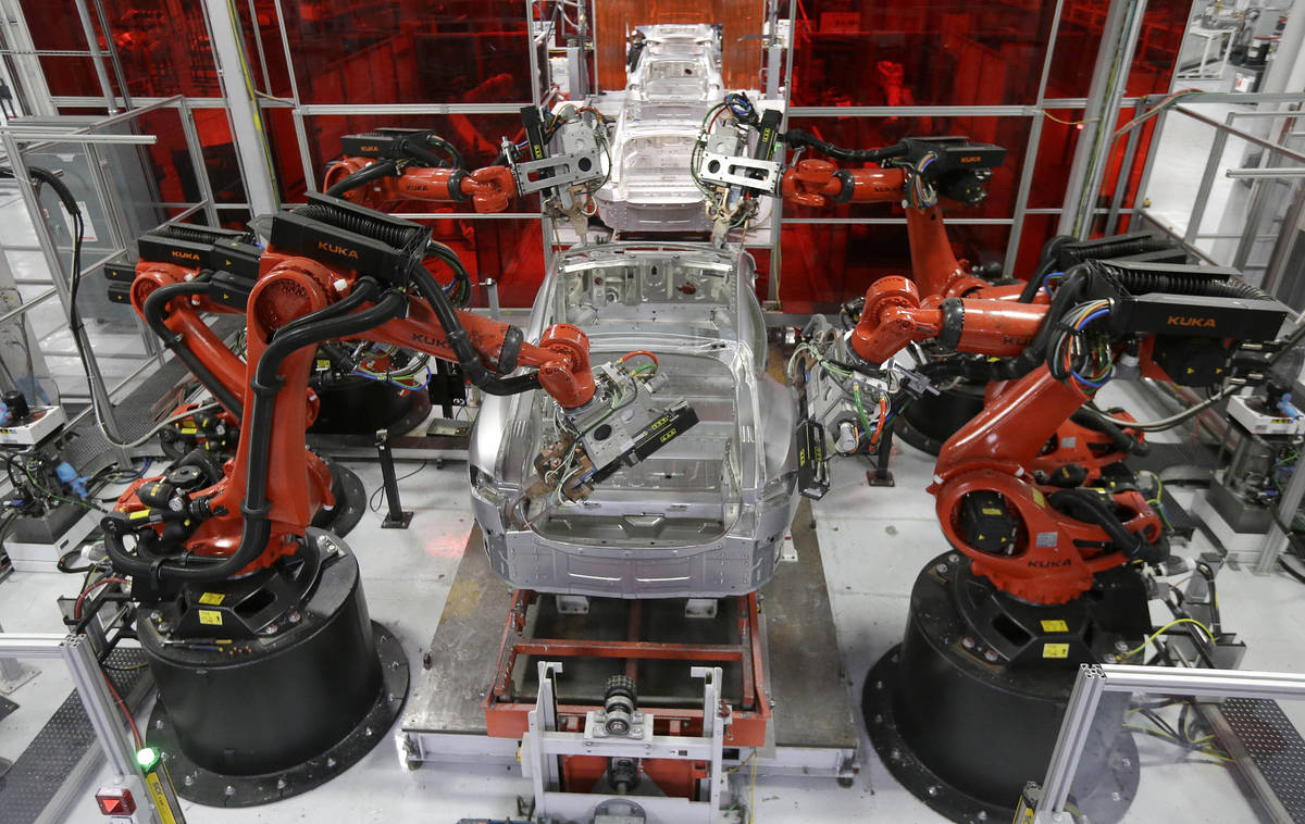 In this May 14, 2015, file photo, Kuka robots work on Tesla Model S cars in the Tesla factory i ...