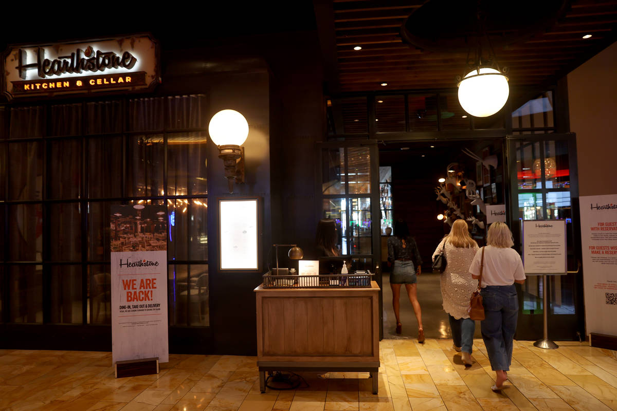 A hostess takes customers to their table at Hearthstone Kitchen & Cellar at Red Rock Resort ...
