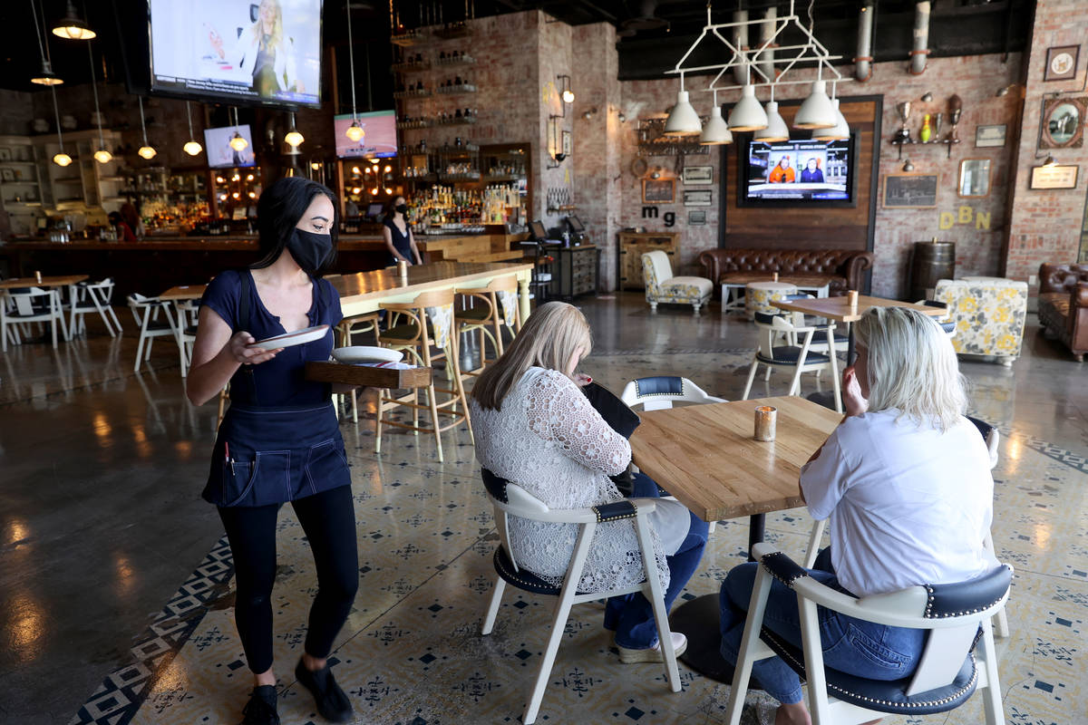 A server sets a customers' table at Hearthstone Kitchen & Cellar at Red Rock Resort in Las ...
