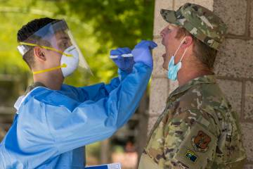 Nevada National Guard soldier PFC Nikolas Herrera, left, inserts a swab into the mouth of Lt. C ...