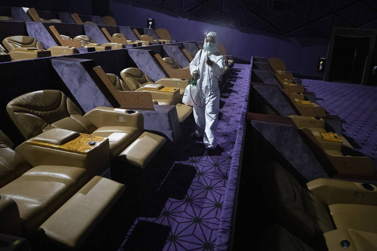 A worker sprays disinfectant as a precaution against the new coronavirus at Quartier Cineart mo ...