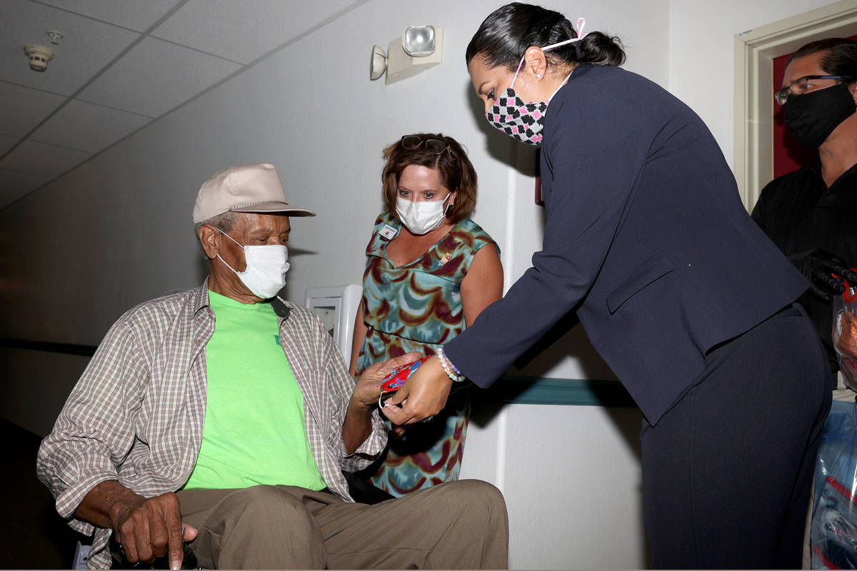 Louis Lewis, 83, receives a washable mask from Las Vegas Councilwoman Olivia Diaz at the Stewar ...
