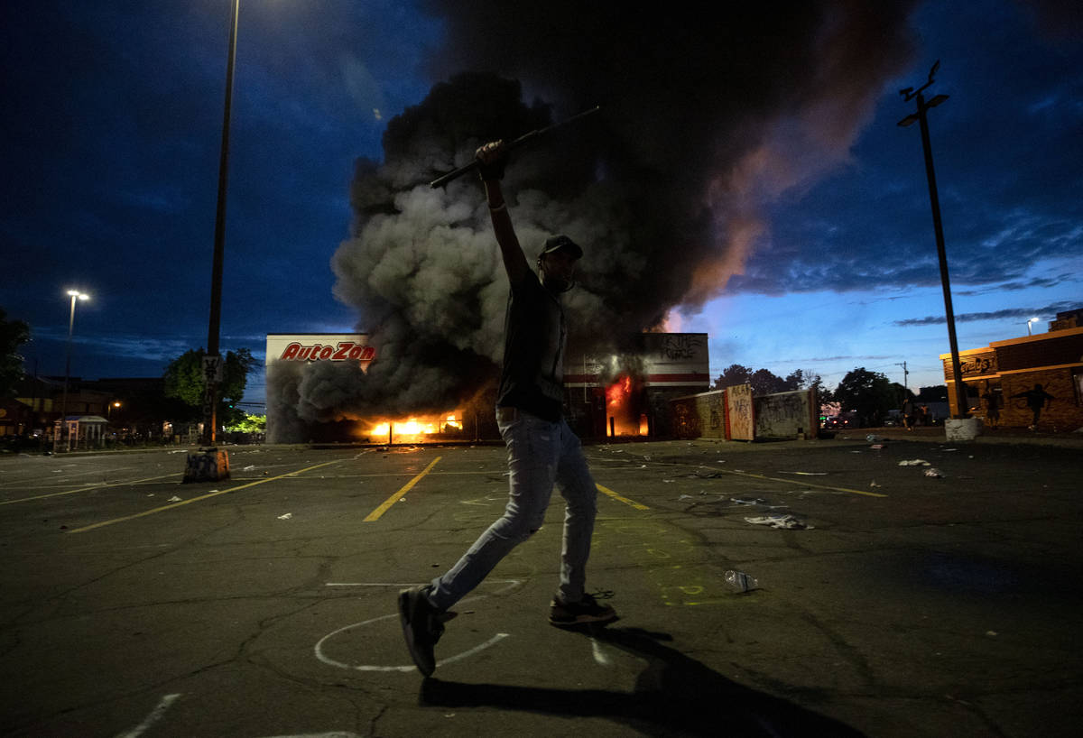 A man poses for a photo in the parking lot of an AutoZone store in flames, while protesters hol ...