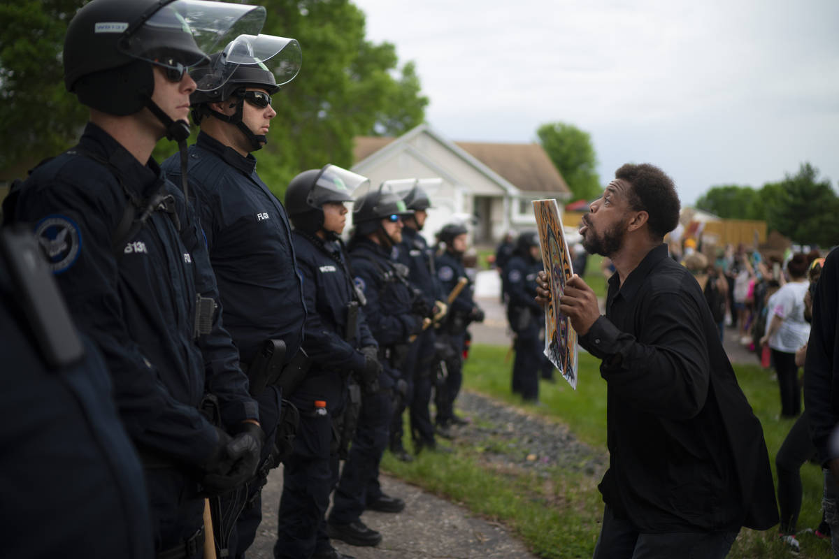 A demonstrator holding a sign jumps up and down so police officers behind the front lines could ...